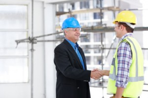 A man in a suit shaking the hand of the foreman on a construction site
