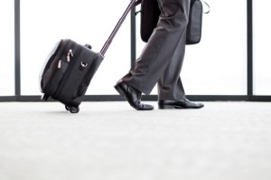 businessman walking in airport with his luggage